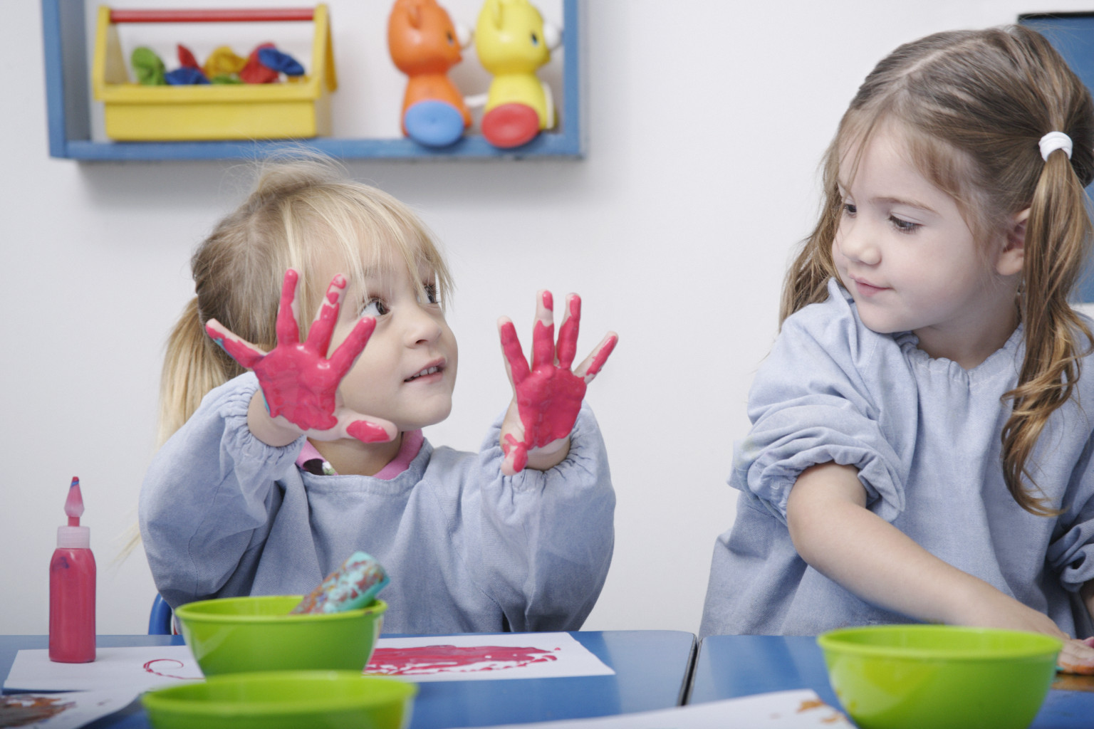 Girls finger-painting in classroom